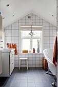 Badezimmer mit weißen Wandfliesen im Dachgeschoss
