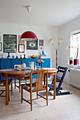 Holztisch mit Stühlen vor blauem Sideboard im Esszimmer