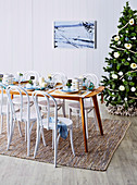 Festive table in front of decorated Christmas tree