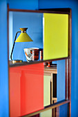 View of table lamp and collection of ceramics on sideboard seen through screen with coloured glass inserts