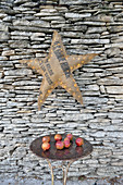Illuminated star made from hessian sack on stone wall