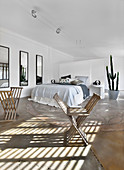 X-chairs in large bedroom in natural shades