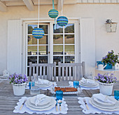 Table with romantic table settings in blue and white on terrace adjoining house