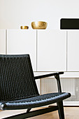 Black chair in front of gold bowls on white sideboard