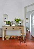 Bar stool in front of console table on hexagonal floor tiles