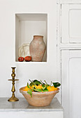 Fresh lemons in terracotta bowl below terracotta jug in niche