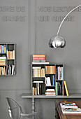 Quadratisches Bücherregal an grauer Kassettenwand mit Schrift