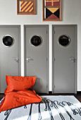 Orange beanbag in front of three grey doors with porthole windows