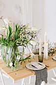Gedeckter Hochzeitstisch mit Tulpenstrauß, trockenen Zweigen und Cylinderkerzen