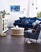 Blue upholstered sofa with pillow collection, upholstered armchair, coffee table and display cabinet in the living room