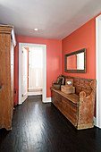 Old church pew in apricot-pink hallway with dark wooden floor