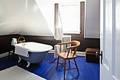 Old chair next to free-standing bathtub on blue-painted wooden floor