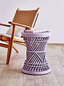 Lilac-colored side table in front of armchair