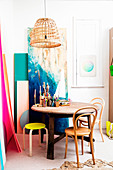Round table with painting utensils, chairs and stools in front of pictures