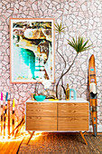 Sideboard with plants in front of wallpapered wall with stone motif