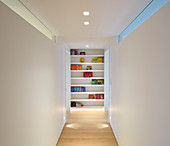 Bookcase at end of corridor with white walls and ceiling