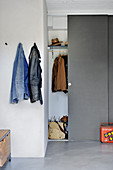 Coat rack behind grey sliding doors and coat pegs on white wall