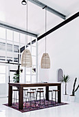 Wooden table with bar stools, above it pendant lights in a high, white room