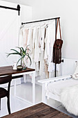 Clothes rack with white clothes next to sofa and table