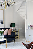 Dark blue sofa with scatter cushions and brass serving trolley in bright living room