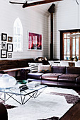 Glass coffee table and vintage leather couch in the living room with white wooden paneling and pointed arch windows in a former church