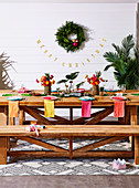 Colorfully laid wooden table with bench against wall with Christmas decoration