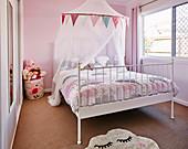 Weisses Bett mit Baldachin in rosa getöntem Mädchenzimmer
