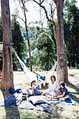 Familie beim Picknicken unter hohen Bäumen im Garten