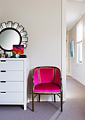 Armchair in pink next to white chest of drawers with mirror