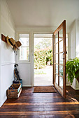 Wardrobe rail with hats and open entrance door in hallway with rustic floorboards