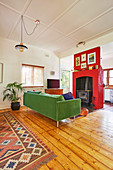 Green sofa and fireplace with red wall covering in the living room with wooden floorboards