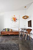 Table with designer chairs in the corner of the room, lowboard and modern art on the wall