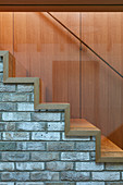 Wooden treads on brick staircase with glass balustrade