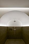 Dusche im halbhoch gefliesten Gewölbe mit indirekter Beleuchtung