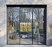 Square window looking into large living room in architect-designed house