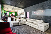 Pale leather couch below modern artwork on black wall in renovated loft apartment