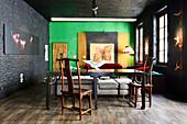 Alter Holztisch mit Stühlen in renoviertem Loft mit schwarzen und grünen Wänden