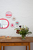 DIY-Dekoration mit Stickrahmen und Botschaft auf weißer Ziegelwand