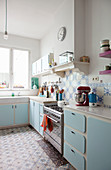 Pale-blue cabinets and patterned tiles in kitchen