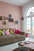 Scatter cushions on sofa in living room of period apartment with patterned wallpaper