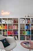Beistelltisch und Klassiker-Schaukelstuhl vor Bücherregal