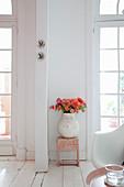 Herbstlicher Blumenstrauß in Vase vor weißer Wand