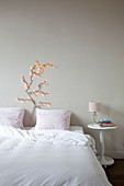 Stylised tree made from fairy lights on wall above double bed in bedroom