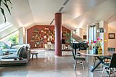 Eleganter Essbereich und Lounge in offenem Wohnraum mit Dachschräge