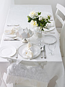 Christmas table set in white, angel wings as chair decoration