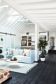 Pale blue loose-covered sofa with scatter cushions in open-plan interior with black wooden floor