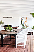 Dining table with rustic wooden top and white rattan chairs on veranda