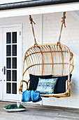 Rattan hanging seat with scatter cushions on veranda