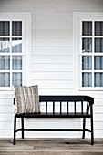 Black wooden bench with scatter cushion outside wooden house
