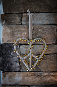 Heart-shaped Christmas decoration covered in tiny golden jingle bells